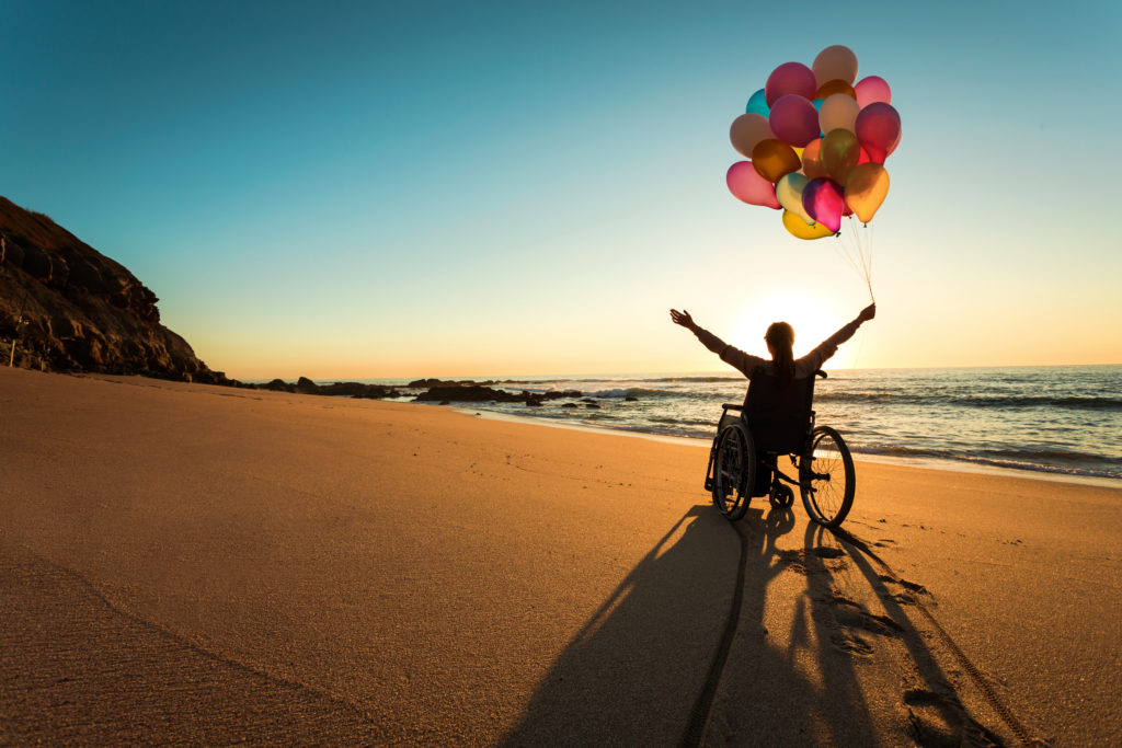 Handicapped person in a wheelchair with colored balloons at the beach