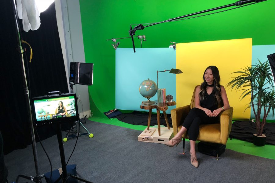 Linda Chau sitting in yellow chair at video shoot
