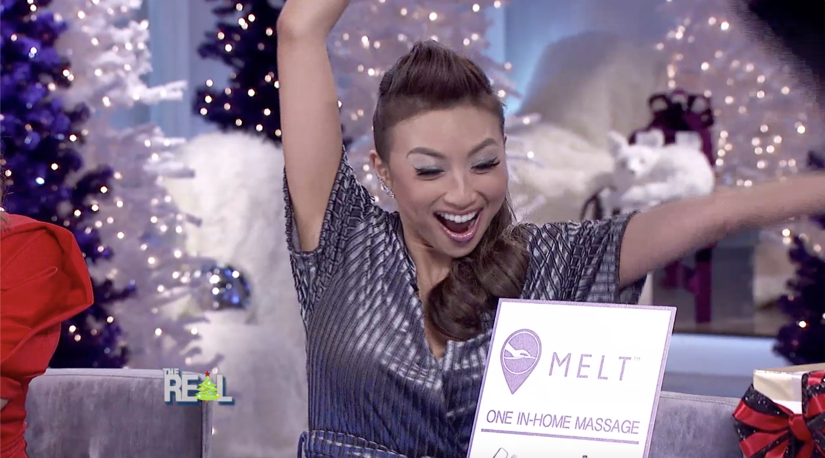 Jeannie Mai opening a present